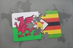 imbarazzi con la bandiera nazionale del Galles e dello Zimbabwe su una mappa di mondo Fotografie Stock Libere da Diritti