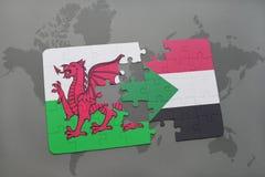 imbarazzi con la bandiera nazionale del Galles e del Sudan su una mappa di mondo Immagine Stock
