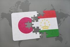 imbarazzi con la bandiera nazionale del Giappone e del Tagikistan su un fondo della mappa di mondo Immagine Stock Libera da Diritti
