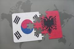 imbarazzi con la bandiera nazionale del Sud Corea ed Albania su un fondo della mappa di mondo Fotografia Stock
