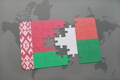 imbarazzi con la bandiera nazionale della Bielorussia e del Madagascar su una mappa di mondo Fotografia Stock