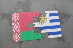 imbarazzi con la bandiera nazionale della Bielorussia e dell'Uruguai su una mappa di mondo Fotografia Stock