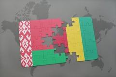 imbarazzi con la bandiera nazionale della Bielorussia e della Guinea su una mappa di mondo Immagine Stock