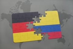 imbarazzi con la bandiera nazionale della Germania e della Colombia su un fondo della mappa di mondo Fotografia Stock