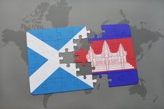 imbarazzi con la bandiera nazionale della Scozia e della Cambogia su una mappa di mondo Immagine Stock
