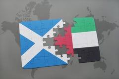 imbarazzi con la bandiera nazionale della Scozia e degli Emirati Arabi Uniti su una mappa di mondo Immagine Stock Libera da Diritti