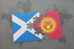 imbarazzi con la bandiera nazionale della Scozia e del Kirghizistan su una mappa di mondo Fotografia Stock