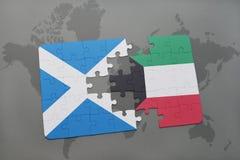 imbarazzi con la bandiera nazionale della Scozia e del Kuwait su una mappa di mondo Immagine Stock Libera da Diritti