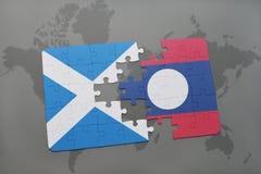 imbarazzi con la bandiera nazionale della Scozia e del Laos su una mappa di mondo Immagine Stock