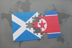imbarazzi con la bandiera nazionale della Scozia e del Nord Corea su una mappa di mondo Immagini Stock