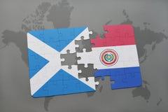 imbarazzi con la bandiera nazionale della Scozia e del Paraguay su una mappa di mondo Fotografia Stock Libera da Diritti