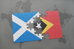 imbarazzi con la bandiera nazionale della Scozia e del Timor Est su una mappa di mondo Fotografia Stock Libera da Diritti