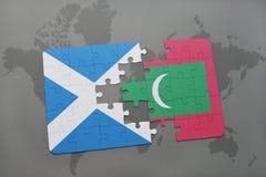 imbarazzi con la bandiera nazionale della Scozia e delle Maldive su una mappa di mondo Immagine Stock Libera da Diritti