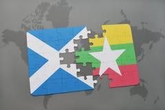 imbarazzi con la bandiera nazionale della Scozia e di myanmar su una mappa di mondo Immagine Stock Libera da Diritti