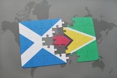 imbarazzi con la bandiera nazionale della Scozia e della Guyana su una mappa di mondo Fotografie Stock Libere da Diritti