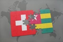 imbarazzi con la bandiera nazionale della Svizzera e del Togo su un fondo della mappa di mondo Immagine Stock