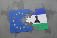 imbarazzi con la bandiera nazionale di Unione Europea e del Lesoto su un fondo della mappa di mondo Immagine Stock