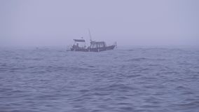 Imbarcazione a motore sola con i turisti o i pescatori nel mare aperto in tempo nebbioso nuvoloso stock footage