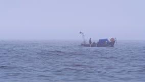 Imbarcazione a motore sola con i turisti o i pescatori nel mare aperto in tempo nebbioso nuvoloso video d archivio