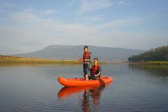 Imbarcazione a remi della figlia e del padre sulle acque calme fotografia stock libera da diritti