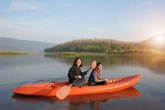 Imbarcazione a remi della figlia e della madre sulle acque calme fotografia stock libera da diritti