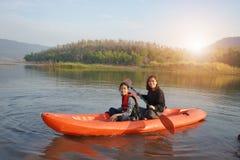Imbarcazione a remi della figlia e della madre sulle acque calme immagine stock libera da diritti
