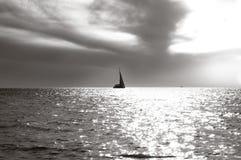 Imbarcazione a vela sola sull'orizzonte e su una superficie regolare del mare in fasci di sole fotografia stock libera da diritti