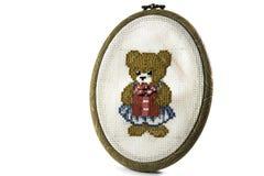 Imbarchi sul ricamo che ha lasciato un orsacchiotto riguarda un fondo bianco isolato Fotografie Stock