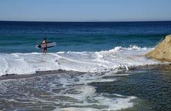 Imbarchi sul surfista che cerca un posto per praticare il surfing alla spiaggia in Laguna Beach, la California di Aliso Fotografia Stock Libera da Diritti