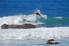 Imbarchi sulla guida del surfista in un'onda al Laguna Beach, CA Immagine Stock