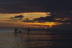 Imbarco della pagaia della gente durante il tramonto Fotografia Stock