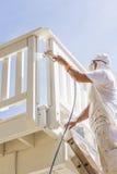 Imbianchino lavorante duro Spray Painting una piattaforma di una casa Fotografia Stock