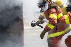 Imbibé deux sapeurs-pompiers de la recherche et de la délivrance de tuyau d'incendie dans t Photos stock