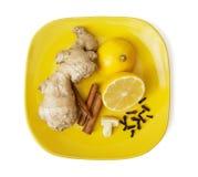Imbir, cynamon, cytryna, czosnek i cloves na koloru żółtego talerzu, zdjęcia stock