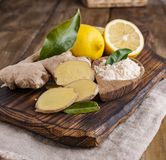 Imbir i cytryna na drewnianym tle, fotografia w nieociosanym stylu Sk?adniki dla grza? i zdrowie napoju alternatywna wanny bambus obrazy stock