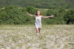 Imbirowa dziewczyna biega na łące fotografia stock