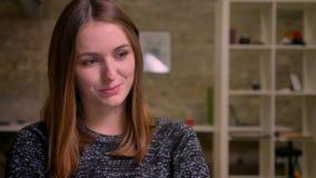 Imbirowa dziewczyna satisfyingly kłama z powrotem na krześle i wtedy opiera jej policzek na jej rękę w biurze zdjęcie wideo