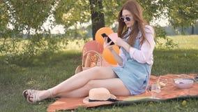 Imbirowa dziewczyna w szkłach i cajgi omijamy robić selfie podczas pinkinu w parku zbiory