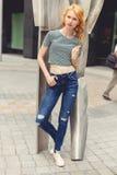 Imbirowa dziewczyna w ulicie obok żelaznej rzeźby, stonowana fotografia Obraz Royalty Free