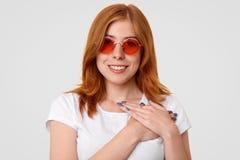Imbirowa kobieta z pozytywnym uśmiechem, utrzymuje ręki na klatce piersiowej, wyraża dobrą postawę, jest ubranym modnych czerwony zdjęcie stock
