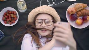 Imbirowa młoda dziewczyna kłama na koc robi śmiesznym twarzom ono filmuje w szkłach zdjęcie wideo