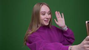 Imbirowy bizneswoman opowiada w videochat na smartphone jest baczny i radosny na zielonym chroma tle zbiory