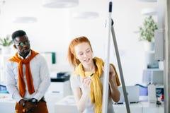 Imbirowy kierownik kobiety writing z piórem na whiteboard dla Afrykańskiego nowego pracownika fotografia stock