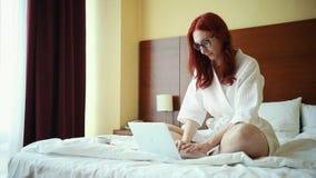Imbirowy uśmiechnięty kobiety obsiadanie na łóżku w działaniu z laptopem i pokoju hotelowym zbiory wideo