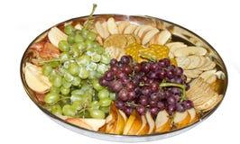 Imbiss-Tellersegment mit Trauben, Frucht-Scheiben und Crackern Lizenzfreies Stockfoto