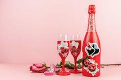 Imbottigli di champagne, i vetri, anello in scatola ed è aumentato su fondo rosa Bottiglia e vetri decorati decorativi fotografia stock libera da diritti