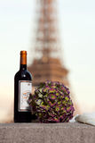 Imbottigli e un mazzo dei fiori vicino alla torre Eiffel Fotografie Stock