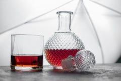 Imbottigli il whiskey ed il vetro di whiskey con ghiaccio e la b vaga luce Immagine Stock Libera da Diritti