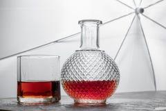 Imbottigli il whiskey ed il vetro di whiskey con ghiaccio su fondo nero Immagine Stock