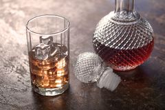 Imbottigli il whiskey ed il vetro di whiskey con ghiaccio su fondo nero Fotografia Stock Libera da Diritti